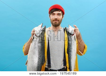 Studio Portrait Of Successful Fisherman Having Blue Appealing Eyes And Thick Dark Beard Holding Two