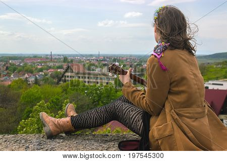 Young woman playing on Ukulele on the roof