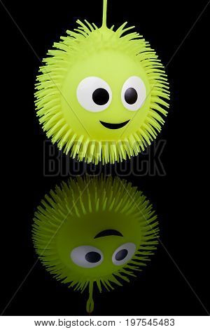 Yellow silicone ball toy with smiling image on black reflecting background