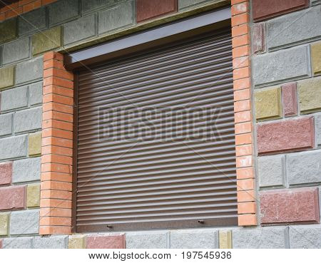 Window with rolling shutter for house protection. Security Shutters Grilles. Shutter security barrier.