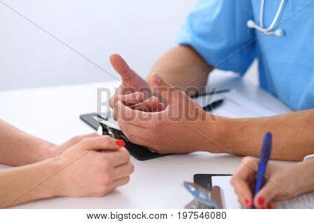 Close up of doctor and patient discussing something while sitting at the table.