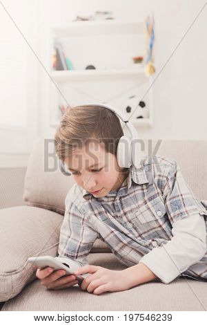 Teenager messaging to friends chat on mobile lying on couch in living room at home