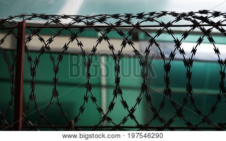 COLOR PHOTO OF SILHOUETTE METAL RAZOR WIRE FENCING