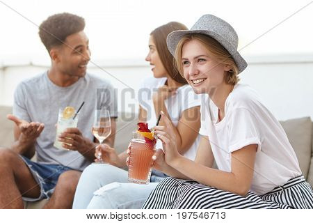 Group Of Three Friends Having Birthday Party Sitting At Cozy Sofa Having Conversation With Each Othe