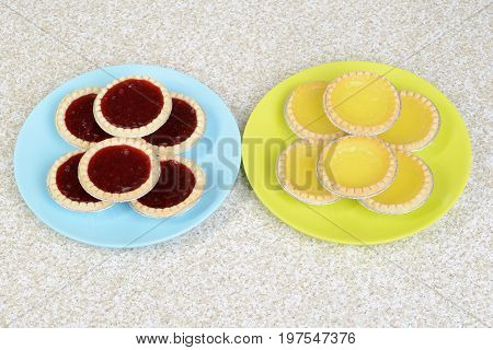 top view strawberry and lemon tarts on plates
