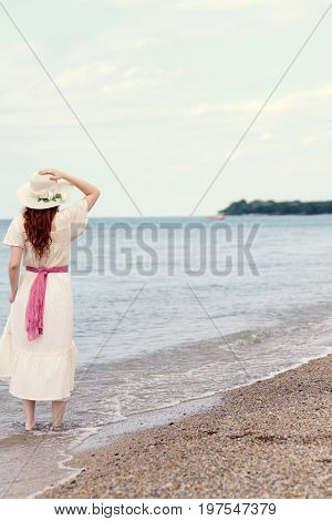 vintage redhead woman at the beach wearing straw hat