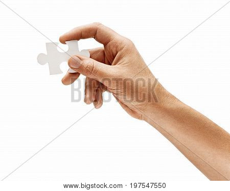Man's hand with one puzzle element isolated on white background. Close up. High resolution product