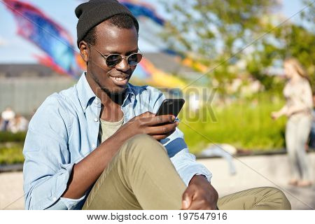 Fashionable Male With Dark Skin And Bristle Sitting Outdoors Checking His News Feed Or Messaging Via