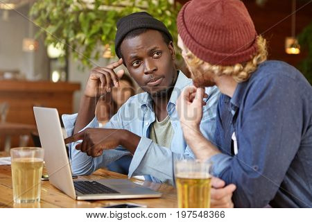 Black Male And His Best Friend Gathering Together At Restaurant Drinking Beer Having Conversation. D
