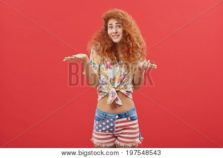 Uncertain Female With Curly Red Hair Shrugging Her Shoulders Having Doubts Not Knowing What To Choos