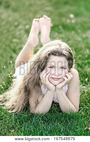 little beautiful girl with long hair on green grass at summer day