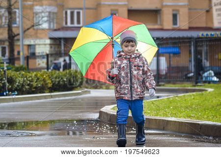 Little boy playing in rainy summer park. Child with colorful rainbow umbrella waterproof coat and boots jumping in puddle and mud in the rain. Kid walking in autumn shower Outdoor fun by any weather.