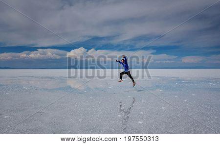 Uyuni, Bolivi March 25, 2017: Man jumping on the lake Salar de Uyuni Bolivia