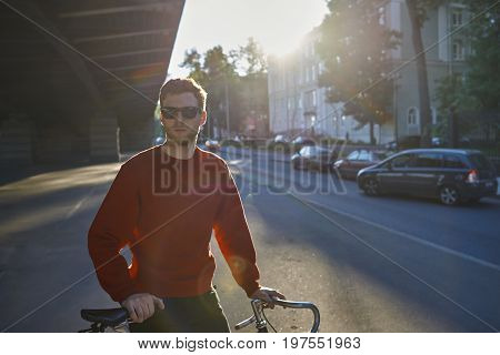 Summer urban shot of handsome bearded hipster in shades standing in the middle of deserted street with bicycle waiting for his friend to join him for morning bike ride sun shining in background