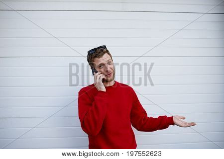 Candid shot of handsome young European man with stubble shrugging shoulders while talking on mobile phone to his girlfriend looking clueless gesturing and saying: I don't know So what Who cares