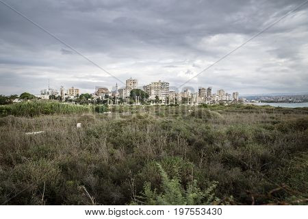 View over grassland to cityscape and ruins with dark dramatic cloudscape in Tyre, Sour, Lebanon