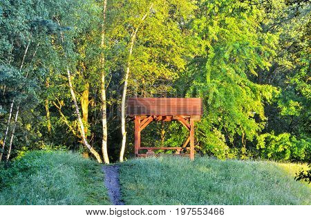 Resting place in the forest. A wooden shed on a green grass.