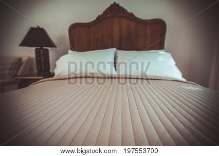 Classic teak wood bed furniture in the warm and cozy bedroom next to the windows with morning sunlight