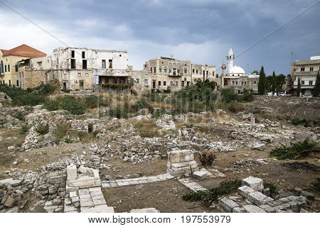 Cityscape with mosque and ruins with dark dramatic cloudscape in Tyre, Sour, Lebanon