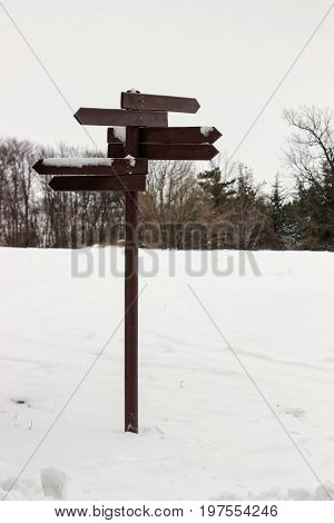 Wooden Direction Sign Covered With Snow