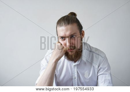 Sadness and boredom concept. Studio shot of unhappy young manager with hair knot and thick beard having upset and bored look feeling tired and pissed off with boring working days at office