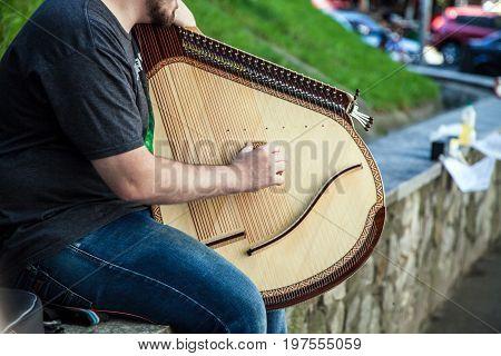 Young guy is playing on Ukrainian national folk instrument bandura