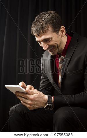 Elegant smiling businessman in black suit is sitting and using tablet on black background.