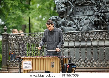 SAINT PETERBURBG, RUSSIA - JULY 1, 2017. Street musician playing the chromatic glockenspiel (metallophone) near the monument to Krylov in the Summer Garden. Saint Petersburg, Russia.