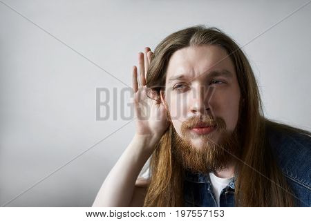 Curious young bearded man wearing his long hair loose holding hand at ear trying to overhear some conversation narrowing eyes posing at blank wall with copy space for your text or information