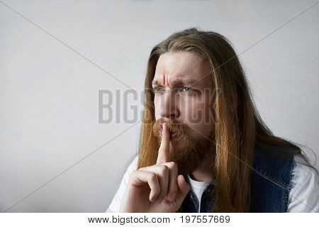 Silence secrecy and conspiracy concept. Picture of unshaven blue-eyed European male in denim vest holding finger at his lips saying Shh asking to keep some confidential information a secret