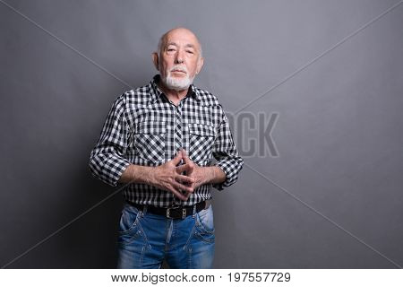 Senior man with public speaker gesture. Fingers connected at fingertips, pose which imposes power and patience, gray studio background, copy space
