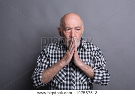 Portrait of hopeful mature man praying, holding hands clasped near face, looking away, gray studio background