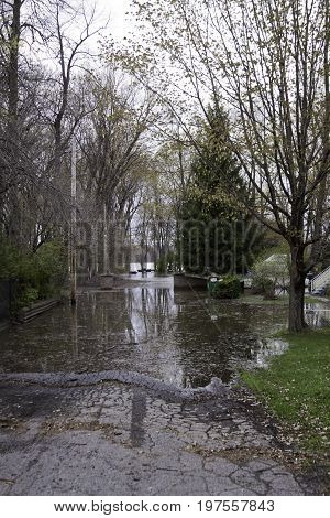 Vertical of flood waters rising over a paved road with trees and foliage partly submerged in the West Island of Montreal, Quebec on a bright overcast day in May.