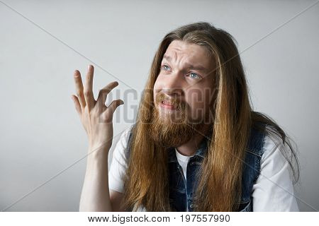 Headshot of emotional young Caucasian male with moustache and beard dressed casually looking up with indignant and frustrated expression making a questioning gesture with hand. Body language
