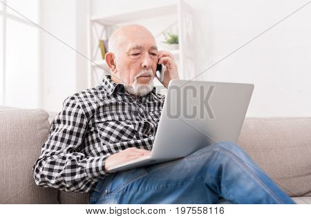 Senior man talking on phone and using laptop, sitting on sofa at home. Modern technology, communication concept