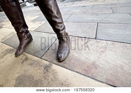 Angled close up of woman's legs and dirty boots