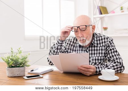 Shocked senior man looking at bills in disbelief, holding his glasses on forehead, copy space