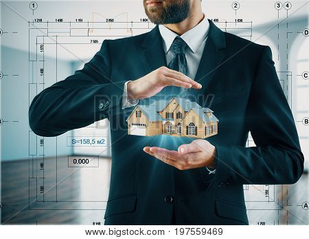 Businessman holding abstract house model in blurry interior with abstract project drawings. Architecture concept. 3D Rendering
