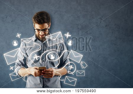 Cheerful young european man using smartphone with abstract email network on concrete wall background. Social media concept