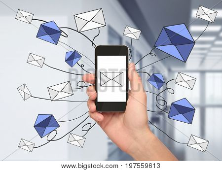 Hand holding smartphone with e-mail network in blurry interior. Email marketing concept. 3D Rendering