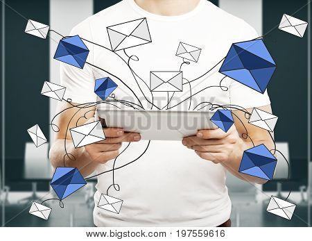Man using tablet with abstract e-mail network in blurry interior. Networking concept. 3D Rendering