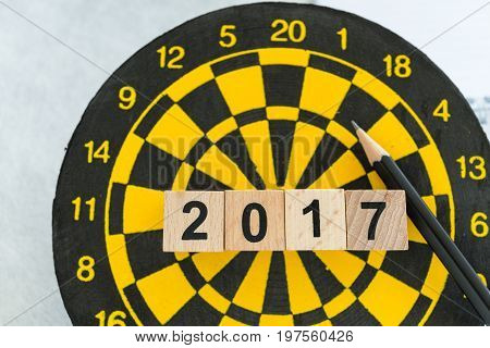 Year check up target concept with wooden blocks number 2017 on dart board and pencil.