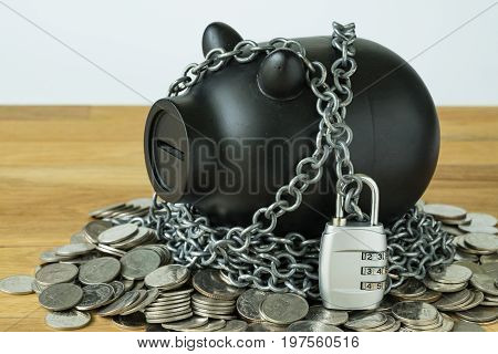 black piggy bank with chains and lock pad on top of coins as security protection or financial saving concept.