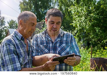 The old and young farmer are discussing about the harvest. They look at the tablet and plan work on the farm. The old farmer passes his experience to his son.