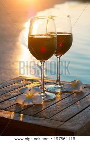 Romantic outdoor scene: two glasses of red wine at sea beach sunset