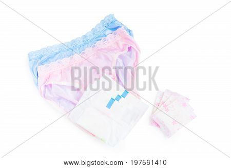 Sanitary napkin and pads in stacks and piles with women's underwear (lingeries) in pink and blue colour over white background with copy space