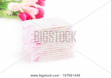 Sanitary napkin pads in stacks for female or woman use on menstrual period days in the month over white background with light pink and strong pink flowers women health and body care concept