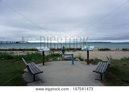 MACKINAW CITY, MICHIGAN / UNITED STATES - JUNE 18, 2017: Visitors may use a telescope, in Alexander Henry Park, to view the Mackinac Bridge, Mackinac Island, and the Straits of Mackinac.