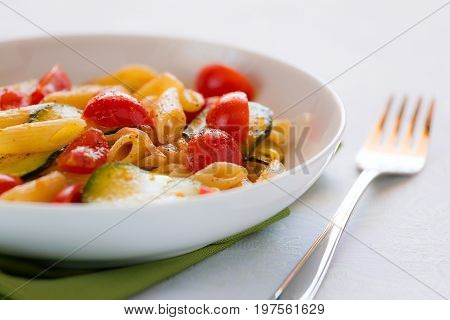 Closeup of traditional italian penne pasta with zucchini and cherry tomatoes seasoned with oil and black pepper