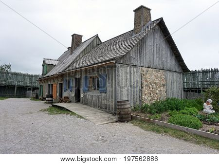 MACKINAW CITY, MICHIGAN / UNITED STATES - JUNE 18, 2017: Visitors may enter a longhouse in Fort Michilimackinac, in the Colonial Michilimackinac State Park, to view the